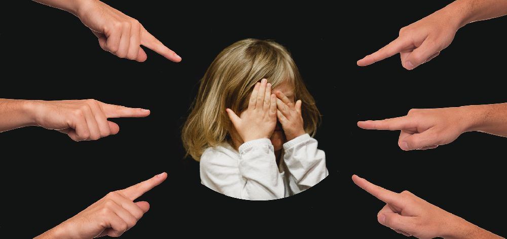 Ein Weinendes Kind in der Mitte des Bildes drum herum viele Hände die auf das Kind zeigen.