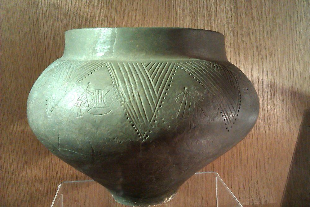 Eine vasenartige Graue Keramik mit ingeritzten verzierungen. es ist ein Strichmännchen zu erkennen, das eine Harfe spielt.