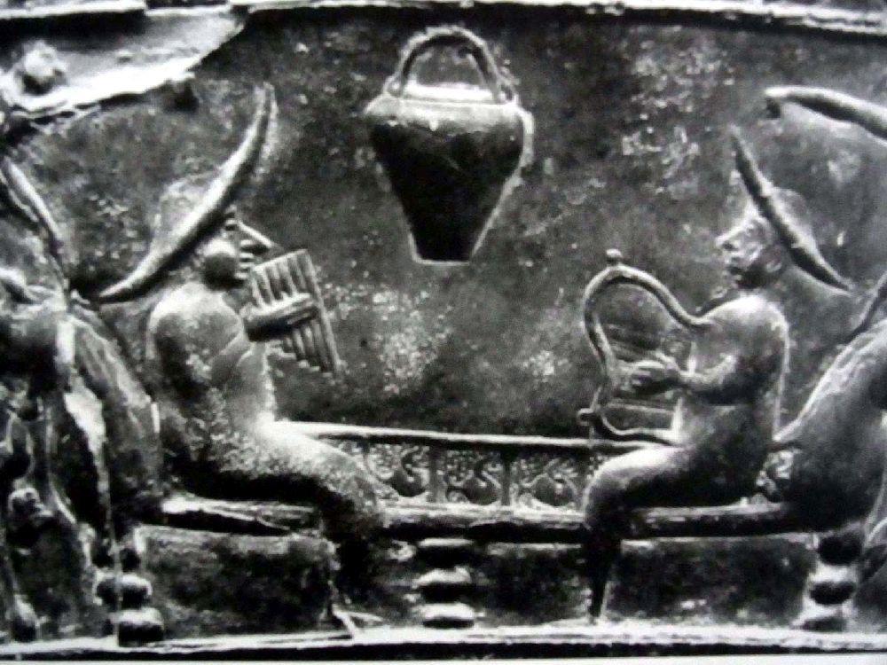 Eine Szene der Bronzesitula Bolonga Certosa. Das Relief zeit zwei Männer die sich auf einer Bank eggenüber sitzen, der Mann zur rechten spiel Panflöte, der zur linken spielt eine Leier. Beide Männert tragen riesiege Sonnenhüte.