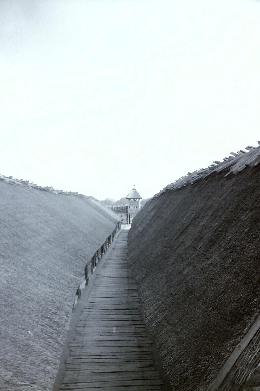 Blick in das Innere Von Biskupin, ein sehr Langer Bohlenweg erstreckt sich zwischen zwei sehr langen Häusern.