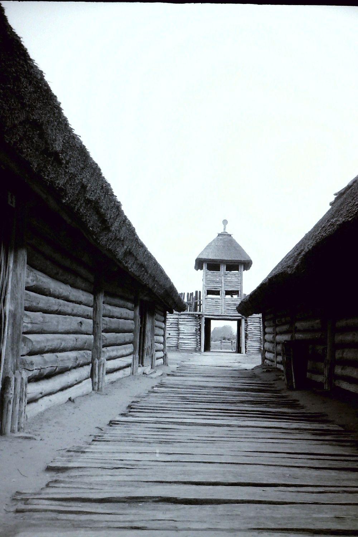 Das Eingangstor von innen in schwarzweißfotografie. Links und recht befinden sich Reihenhäuser, in der Mitte ein Bohlenweg und am Ende ein riesieges Tor
