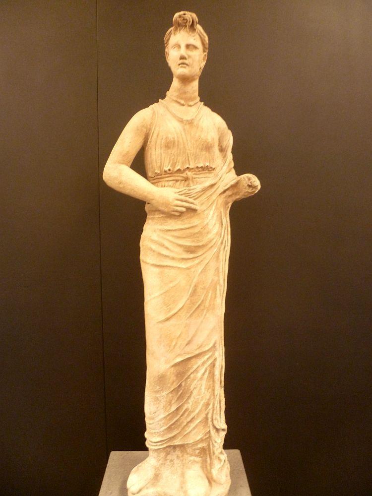 Mädchen aus Etrurien, hergestellt c.a. 250 v. Chr.. Das Mädchen trägt eine Strinknotenfristur. Die Figur ist freihändig modelliert und überlebensgroß. Das ist eine sehr seltene Darstellungsart der Etrusker.